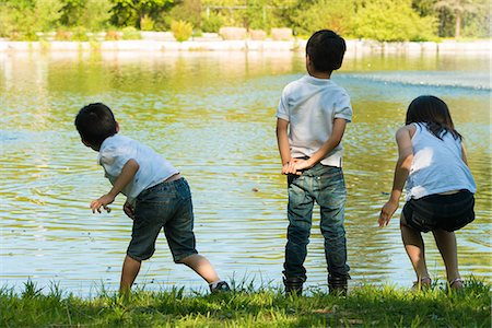 playing - Three children playing by lake Stock Photo - Premium Royalty-Free, Code: 614-07031211