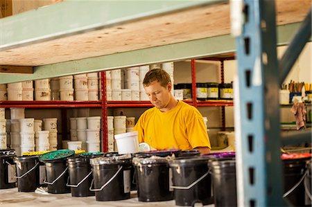 Man checking ink in screen print workshop Stock Photo - Premium Royalty-Free, Code: 614-07031282