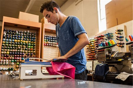 Worker using embroidery machine in t-shirt  printing workshop Stock Photo - Premium Royalty-Free, Code: 614-07031296