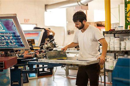Worker pressing ink on frame in screen printing workshop Stock Photo - Premium Royalty-Free, Code: 614-07031299