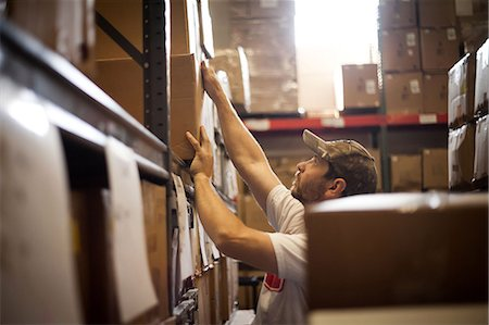 piles of work - Worker reaching up for cardboard box stored in warehouse Stock Photo - Premium Royalty-Free, Code: 614-07031311