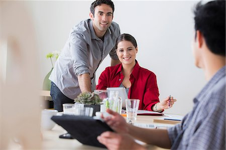 Office workers chatting at desk Stock Photo - Premium Royalty-Free, Code: 614-07031367