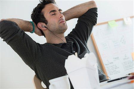 Portrait of male listening to earphones Stock Photo - Premium Royalty-Free, Code: 614-07031401