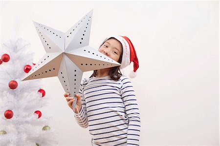 stars on white background - Girl holding up Christmas star, portrait Stock Photo - Premium Royalty-Free, Code: 614-07031465