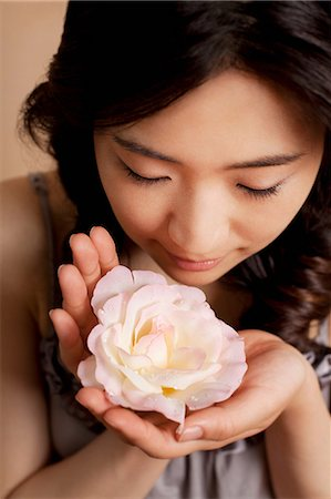 smelling - Young woman smelling flower, close up Stock Photo - Premium Royalty-Free, Code: 614-07031460