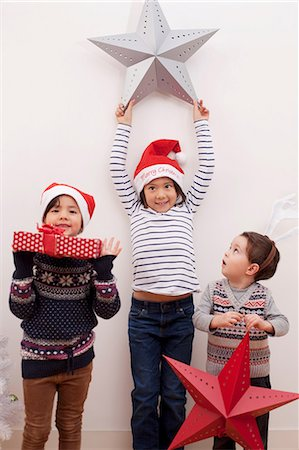 stars on white background - Children holding up Christmas decorations Stock Photo - Premium Royalty-Free, Code: 614-07031463