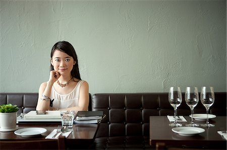 Young woman in restaurant, hand on chin Stock Photo - Premium Royalty-Free, Code: 614-07031505