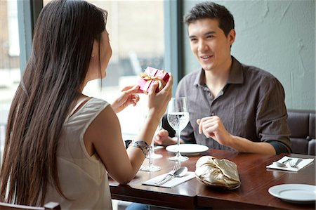 restaurant - Young couple in restaurant, woman holding gift box Stock Photo - Premium Royalty-Free, Code: 614-07031518