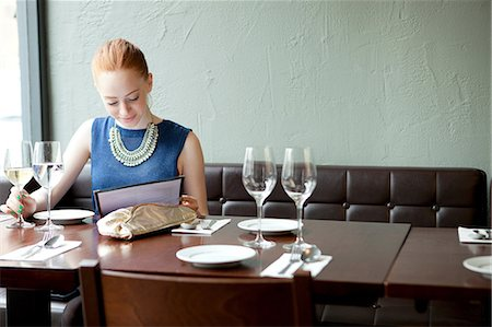 Young woman in restaurant, reading menu Stock Photo - Premium Royalty-Free, Code: 614-07031525