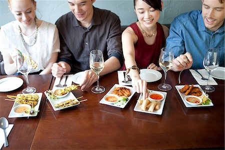 restaurant - Four friends eating food in restaurant Stock Photo - Premium Royalty-Free, Code: 614-07031531