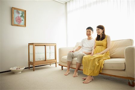 pregnant asian - Man and pregnant woman sitting on sofa Stock Photo - Premium Royalty-Free, Code: 614-07031599