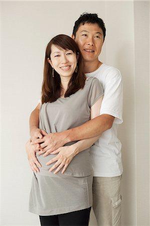 pregnant asian - Man hugging pregnant woman, portrait Stock Photo - Premium Royalty-Free, Code: 614-07031593