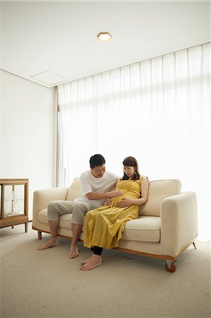 pregnant couple couch - Man touching pregnant woman's stomach on sofa Stock Photo - Premium Royalty-Free, Code: 614-07031601