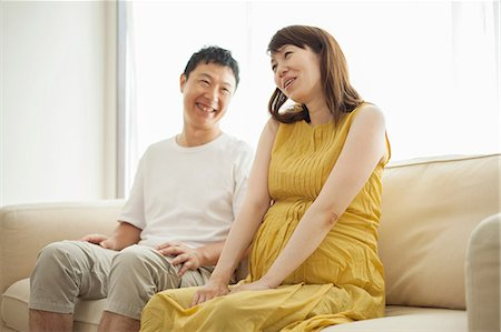 pregnant couple couch - Man and pregnant woman sitting on sofa Stock Photo - Premium Royalty-Free, Code: 614-07031603