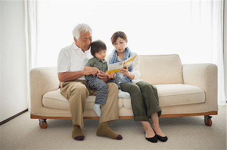 Mother reading to son sitting on grandfather's lap Stock Photo - Premium Royalty-Free, Code: 614-07031631