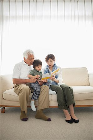 Mother reading to son sitting on grandfather's lap Stock Photo - Premium Royalty-Free, Code: 614-07031632