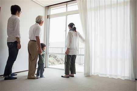 Three generation family standing by window Stock Photo - Premium Royalty-Free, Code: 614-07031644