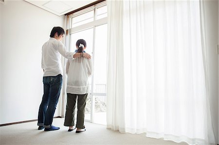 Couple standing by window Stock Photo - Premium Royalty-Free, Code: 614-07031645