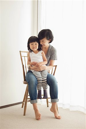 Mother and daughter sitting on wooden chair, portrait Stock Photo - Premium Royalty-Free, Code: 614-07031648
