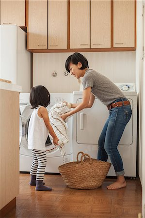 Mother and daughter putting towel into washing machine Stock Photo - Premium Royalty-Free, Code: 614-07031655