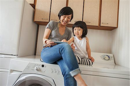 Mother and daughter sitting on washing machine using tablet Stock Photo - Premium Royalty-Free, Code: 614-07031658
