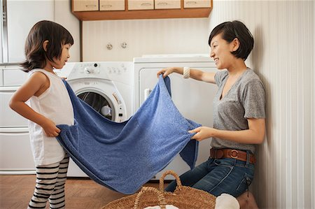 Mother and daughter folding towel Stock Photo - Premium Royalty-Free, Code: 614-07031659