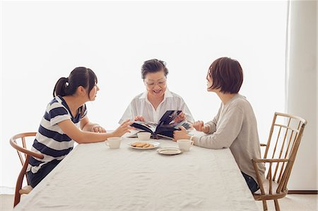 Three generation family looking at photograph album Stock Photo - Premium Royalty-Free, Code: 614-07031668