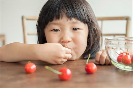 Girl eating cherries, portrait Stock Photo - Premium Royalty-Free, Code: 614-07031689
