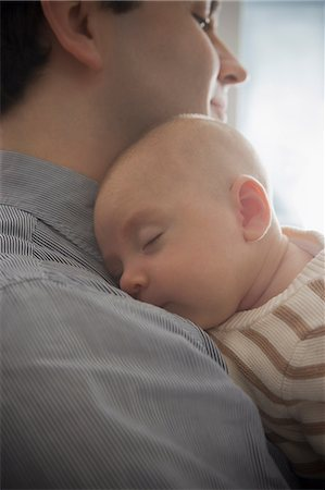 Baby boy sleeping on father's shoulder, close up Stock Photo - Premium Royalty-Free, Code: 614-07031694