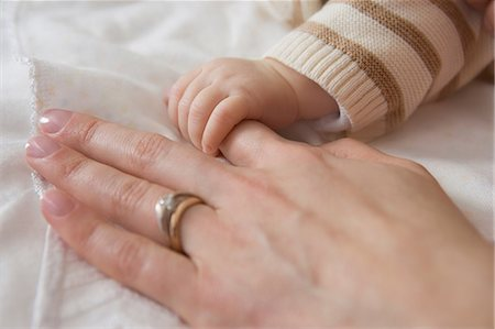 Baby boy holding mother's hand, close up Stock Photo - Premium Royalty-Free, Code: 614-07031697