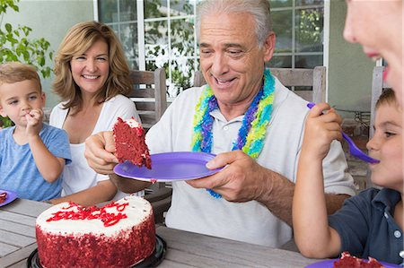 Senior man serving slice of birthday cake at party with family Stock Photo - Premium Royalty-Free, Code: 614-07031714