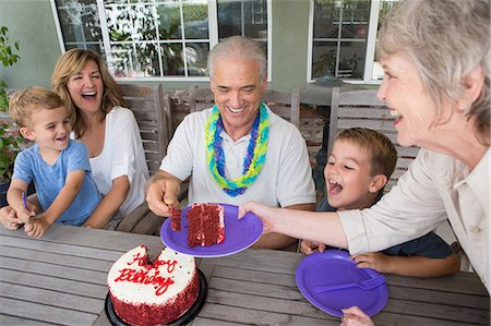 Senior woman serving slice of birthday cake at party with family Stock Photo - Premium Royalty-Free, Code: 614-07031713