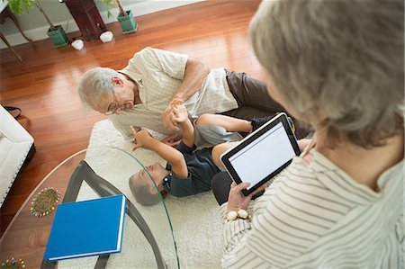 Senior man tickling grandson on rug Stock Photo - Premium Royalty-Free, Code: 614-07031721