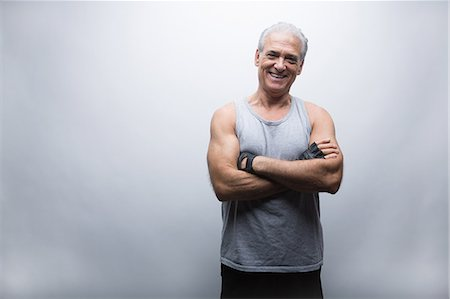 Senior man in sports clothing with arms crossed, portrait Stock Photo - Premium Royalty-Free, Code: 614-07031736