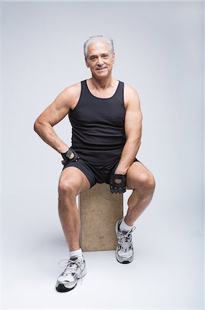 fit people - Senior man in sports clothing sitting in studio, portrait Stock Photo - Premium Royalty-Free, Code: 614-07031757