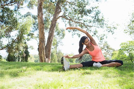 stretching (people exercising) - Young woman stretching in park Stock Photo - Premium Royalty-Free, Code: 614-07031775