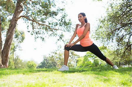 stretching (people exercising) - Young woman stretching in park Stock Photo - Premium Royalty-Free, Code: 614-07031776