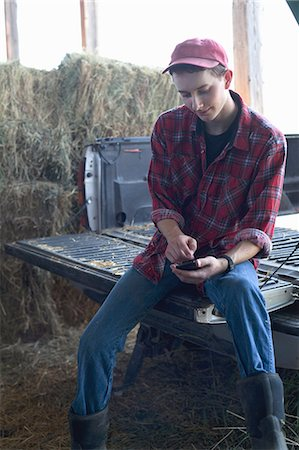 farm phone - Young farmer sitting and using mobile phone Stock Photo - Premium Royalty-Free, Code: 614-07031797
