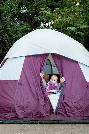 Toddler twins and father peeking out of tent Stock Photo - Premium Royalty-Free, Code: 614-07031803