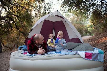 Toddler twins on camping mattress with father Stock Photo - Premium Royalty-Free, Code: 614-07031829