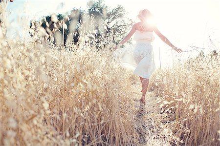 Woman walking through field touching grasses Stock Photo - Premium Royalty-Free, Code: 614-07031820