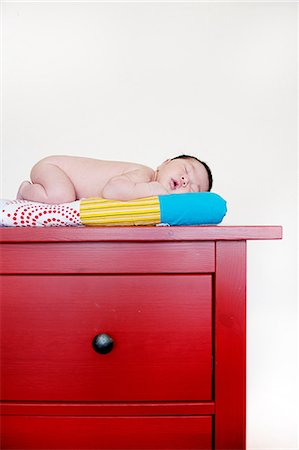 sleeping nude - Baby boy sleeping on top of red drawers Stock Photo - Premium Royalty-Free, Code: 614-07031844