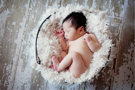 sleeping nude - Baby boy sleeping in fur lined basket Stock Photo - Premium Royalty-Free, Code: 614-07031850