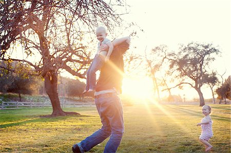 Father carrying son in sunlit field Stock Photo - Premium Royalty-Free, Code: 614-07031877