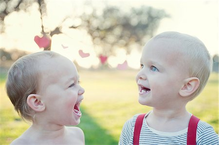 Brother and sister laughing outdoors Stock Photo - Premium Royalty-Free, Code: 614-07031873