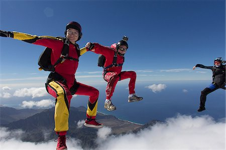 Small group of skydivers reaching to join hands Stock Photo - Premium Royalty-Free, Code: 614-07031895