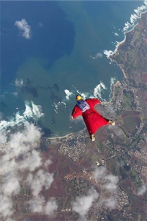 fly - Woman in wingsuit flying above Honolulu, Hawaii Stock Photo - Premium Royalty-Free, Code: 614-07031897