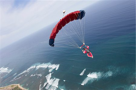 Skydiver with red parachute above Honolulu, Hawaii Stock Photo - Premium Royalty-Free, Code: 614-07031900