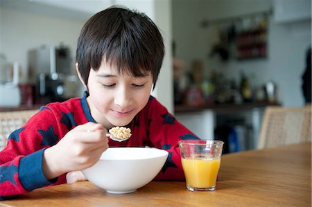 Boy eating breakfast cereal at table Stock Photo - Premium Royalty-Free, Code: 614-07032019