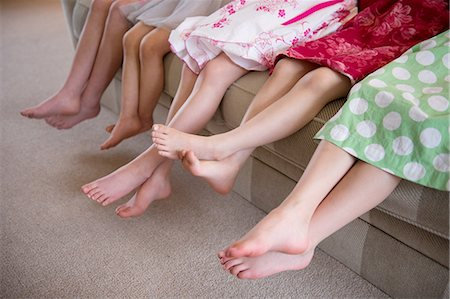 preteen asian girls - Girls sitting together in a row on sofa Stock Photo - Premium Royalty-Free, Code: 614-07032044